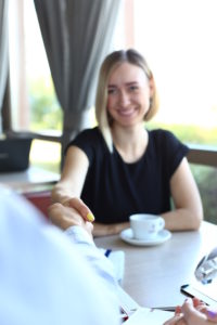 Smiling man and woman shake hands as hello in cafe portrait. Friend welcome mediation offer positive introduction greet or thanks gesture summit participate approval strike arm bargain concept
